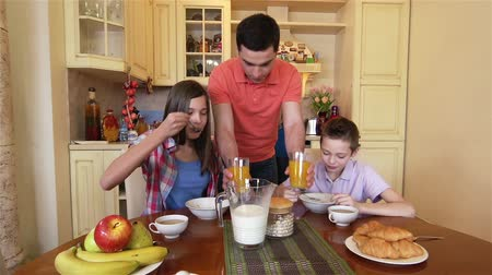 kahvaltı : Kids having a healthy meal in the morning, father bringing fresh juice Stok Video