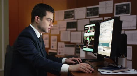 analyzovat : Young businessman being concentrated on the stock market data displayed on the monitor