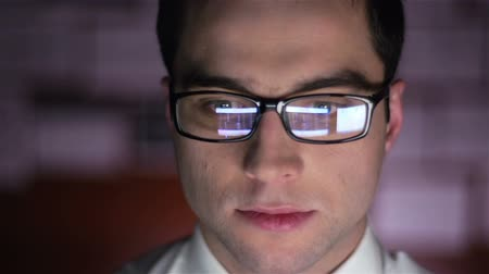 экономика : Close-up of a financial broker with stock exchange data reflecting in his glass lenses Стоковые видеозаписи