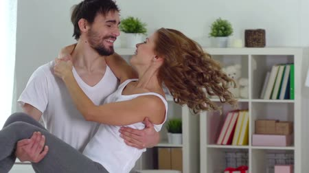 transportar : Slow-motion of a happy guy carrying his girlfriend in his arms