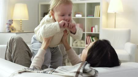tenderness : Slow motion of a charming young mother playing with her kid