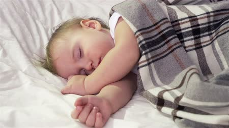 repousante : Tot sleeping peacefully under a woolen plaid  Stock Footage