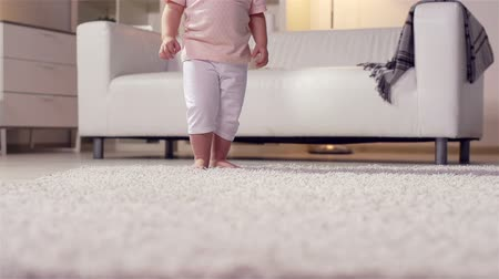 halı : Little kid making a step after step across the carpet