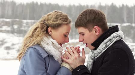 holding : Caring guy warming the hands of his girlfriend