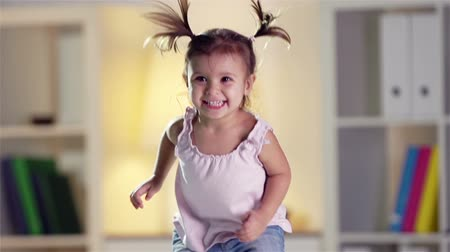little : Slow-motion of a cheerful little cutie jumping happily at home  Stock Footage