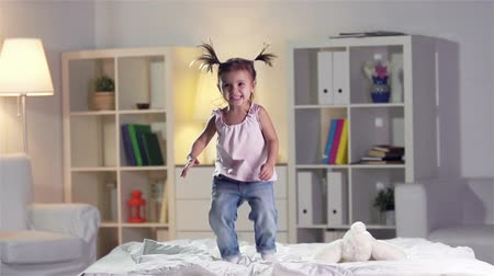 salto : Slow-motion of a carefree girl jumping on the bed  Stock Footage