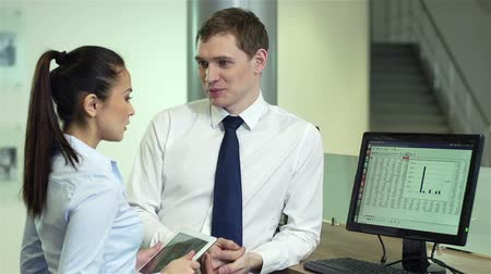 консалтинг : Successful business worker consulting his pretty colleague on financial issues Стоковые видеозаписи
