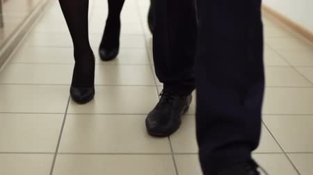 компания : Slow-motion of a business team following the office corridor, only legs are viewed Стоковые видеозаписи