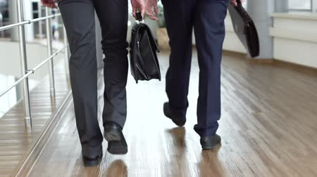 ayaklar : Elegant businessmen viewed from behind walking together across the office building Stok Video