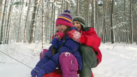 сестра : Boy and girl sledding together, boy falling off the sled
