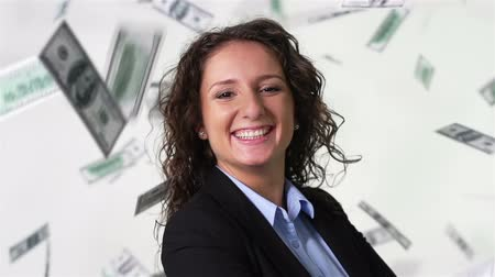 bajnok : Close-up of a lovely businesswoman smiling at camera, money falling all around her Stock mozgókép