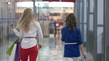покупка товаров : Cheerful shoppers walking along the mall corridor viewed from behind
