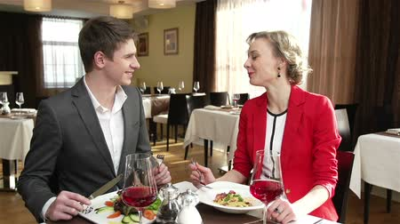 обедающий : Young people dining at the restaurant, man sharing his dish with his girlfriend  Стоковые видеозаписи