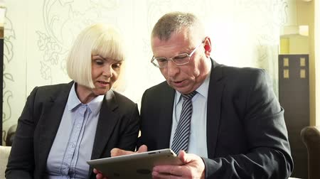 консультант : Modern mature business people using touchpad in their teamwork