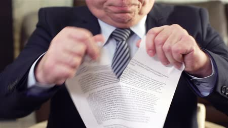 papelada : Slow-motion of a serious businessman tearing a contract in pieces