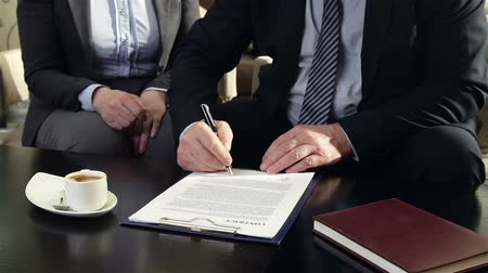 legal : Partners signing contract and shaking hands