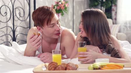 amantes : Lovely sweethearts eating their delicious breakfast lying in bed