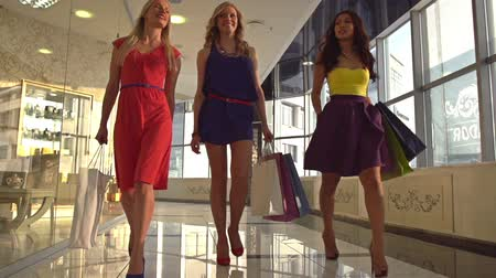 покупатель : Group of friendly females chatting while walking in the mall