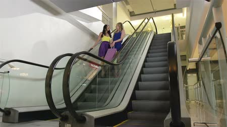 mozgólépcső : Ladies descending on escalator while doing shopping in the mall