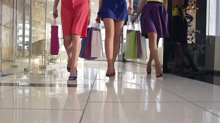 покупатель : Legs of shopaholics with shopping bags walking down mall Стоковые видеозаписи