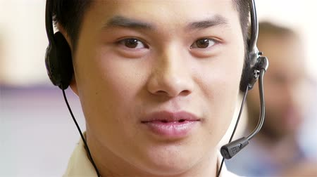 telecoms : Asian man using headset talking to a client looking straight at camera Stock Footage