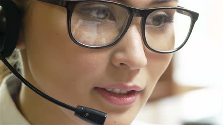 espetáculos : Pretty operator in headphones consulting a client and putting on eyeglasses