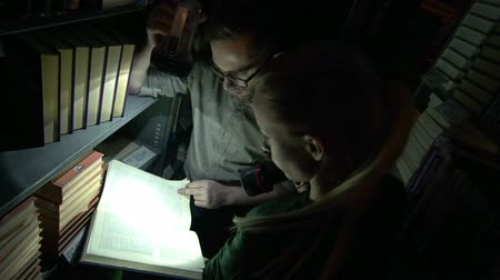 arquivos : Man and woman turning over the pages of the book and lighting it with a flash-light