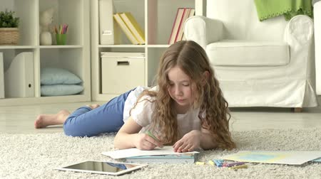 Пол : Youngster lying on the floor and drawing with crayons Стоковые видеозаписи