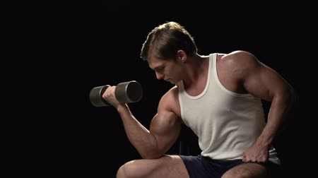 atleta : Brutal man pumping up arms muscles sitting on the bench