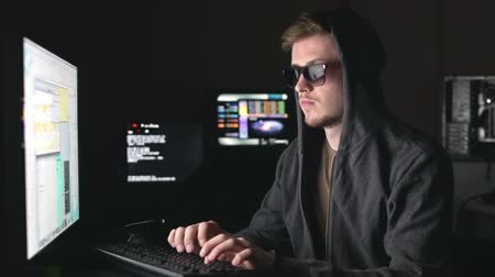 хакер : Bearded guy wearing light-protective spectacles and hood, typing on keyboard in the darkness