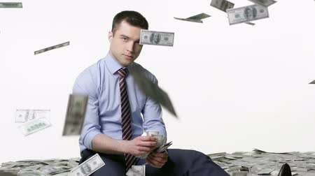 zengin : Man sitting and counting money, bills falling from above