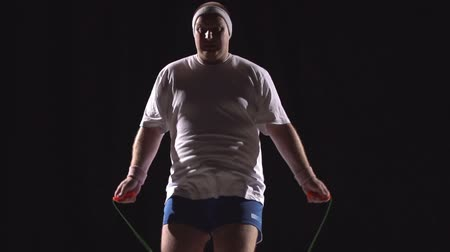 nadváha : Slow-mo of stout man jumping rope against black background