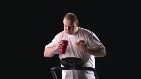 потеря : Man eating and drinking on the treadmill in the darkness Стоковые видеозаписи