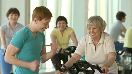 stimulating : Young instructor motivating senior woman to cycle faster