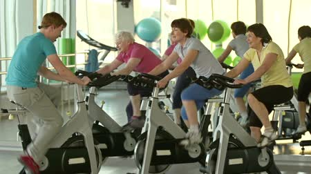 stimulating : Side view of cycling workout of three women and male instructor with headset