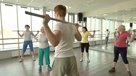 группа : Male fitness professional instructing female group at toning bar exercise