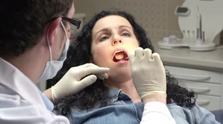 boca aberta : Female patient's teeth examined by male doctor, woman smiling happy with a result Stock Footage