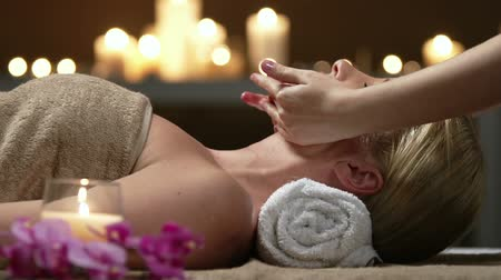 estância termal : Unrecognizable masseuse performing facial massage for blonde young lady resting head on towel roll Vídeos