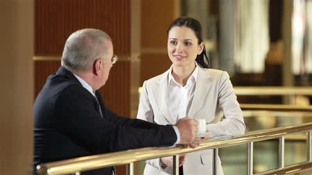 irodaház : Man with cup of coffee leaning on railing and having formal conversation with young coworker