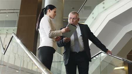 titkár : Tilt up of mature boss and young secretary having discussion at staircase with the help of portable tab