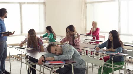 profesor : Static shooting of group of students at class, young tutor lecturing and one of students dozing Wideo