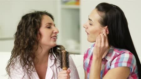 earpiece : Girls singing to music, one using comb as microphone
