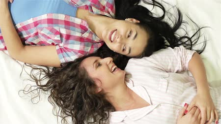 paylaşımı : High angle of friends resting on the bed, having cheerful conversation and getting up
