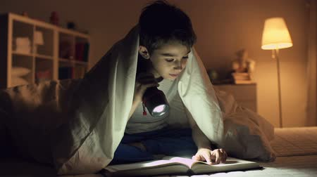 probudit : Static shot of boy sitting under blanket and reading a book