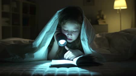 zvědavý : Dolly of girl resting in bed and reading aloud with the help of lantern Dostupné videozáznamy