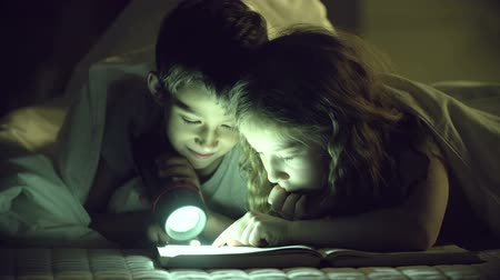 cozy : Static shooting of two youngsters searching lines in the book Stock Footage