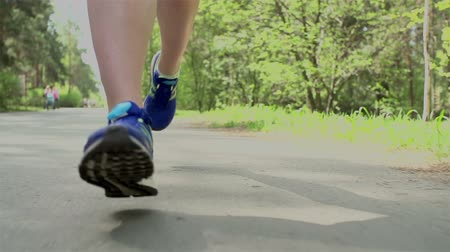 sapato : Tracking close up on legs of unrecognizable woman jogging on track outdoors in slow-mo Vídeos