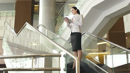 КПК : Dolly of business lady standing on stairs and using PDA