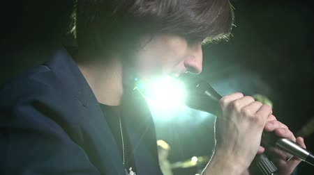 cantora : Handheld close up of handsome performer whispering and screaming in microphone on stage