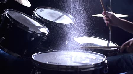 loud music : Close up of drums perfused with water for special effect hit by unrecognizable guy in slow motion